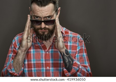 No jokes. Cropped shot of a bearded tattooed guy holing his glasses looking to the camera confidently on black background at the studio.