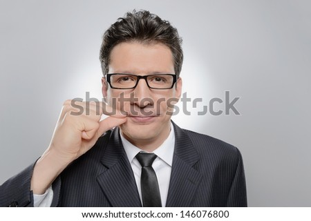 No more word. Portrait of confident businessman holding his finger on the lips and looking at camera - stock photo