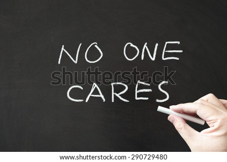 No one cares words written on blackboard using chalk - stock photo