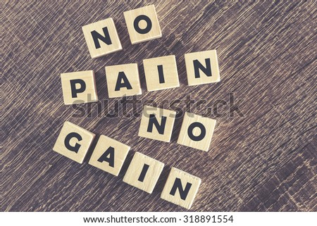 No Pain No Gain message written with wooden blocks on a wooden table. Image cross processed for grunge look - stock photo