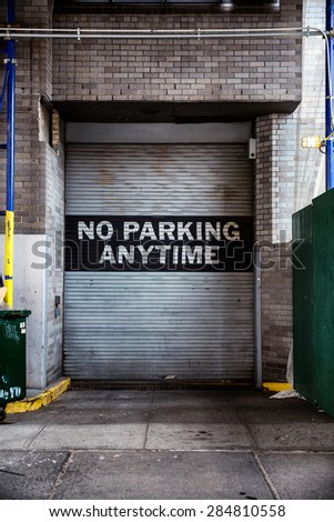 No parking anytime sign on the metal garage gate. - stock photo