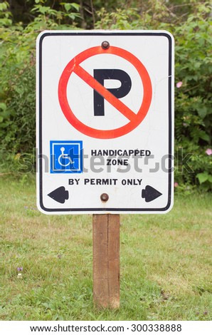 No parking in handicapped zone sign. Sign on grass area.