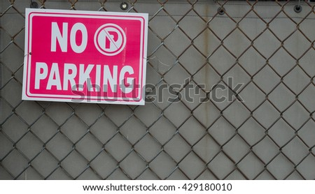 No parking sign on chain link fence background - stock photo