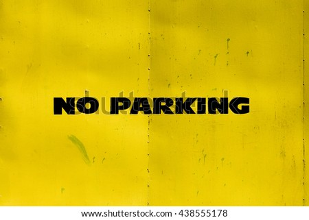no parking sign on yellow metal gate