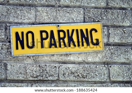 No parking yellow sign plate on a grungy brick wall  - stock photo