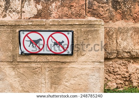 No Pets Allowed Signs on Old Textured Wall  Conceptual No Dog and Cat Pets Allowed Signs on Old Textured Brown Wall  Closeup of park scene for book cover, brochure, magazine, CD cover design, website - stock photo
