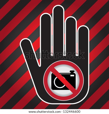 No Photo or No Camera Prohibited Sign Present By Hand With No Camera Sign Inside in Caution Zone Dark and Red Background