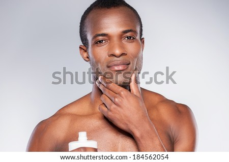 No skin irritation. Young shirtless African man applying cream at his face and looking at camera while standing against grey background - stock photo