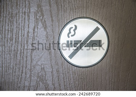 No Smoking gray round plastic health symbol on brown wooden pattern wall door in hotel restaurant living room  Empty copy Non-smoking space for incription Sign on metal texture Crossed Cigarette smoke - stock photo