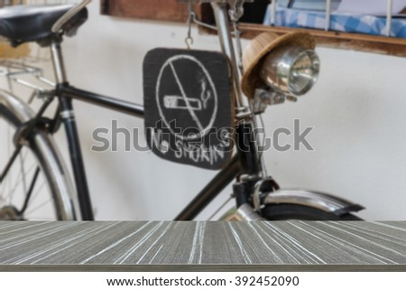 no smoking hand writing sign on the black bicycle (blur background and wooden table for displaying your product)
