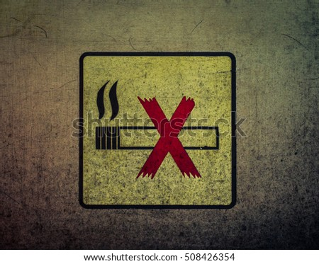 no smoking sign on the dirty metal wall .