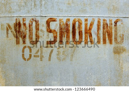 No smoking warning on an old derelict oil tank - stock photo