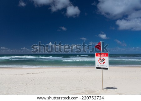 No swimming flag on the beach after storm - stock photo