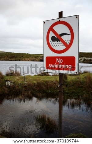 No Swimming Sign next to Open Water, Dartmoor, Devon, UK - stock photo