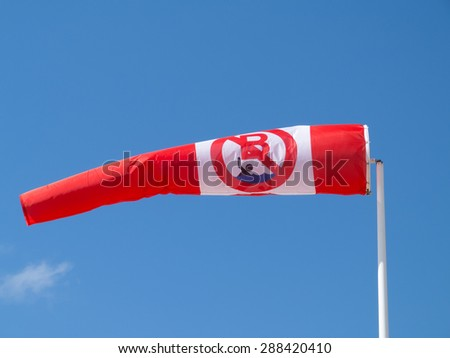 No swimming, unguarded zone, windsock on blue sky - stock photo