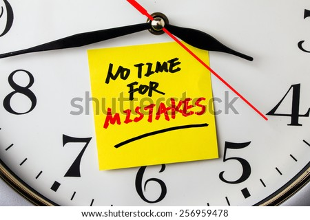 no time for mistakes on post-it stuck to a wall clock - stock photo