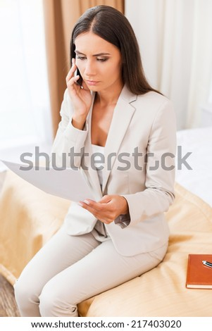 No time to relax. Top view of confident young businesswoman in suit talking on the mobile phone and holding document while sitting on the bed in hotel room - stock photo