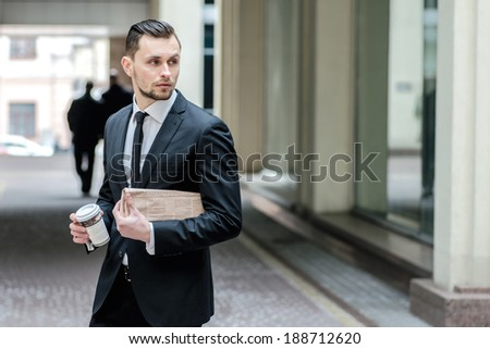 No time to rest. Confident businessman holding a newspaper and coffee. A young man goes to work - stock photo