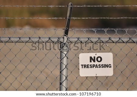 No trespassing sign hanging on a menacing barbed wire fence - stock photo