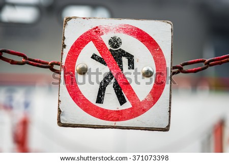 No trespassing sign hanging on the red chain. Shallow depth of field - stock photo