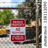 no trespassing sign on private property fence; violators will be prosecuted - stock photo