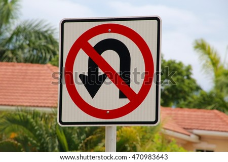 No U-Turn Sign Houses in Background