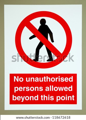 no unauthorised persons allowed beyond this point sign on a gray wall - stock photo