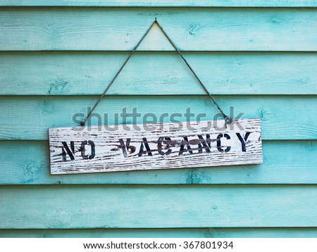 No Vacancy sign hanging on blue or aqua painted cedar siding. - stock photo