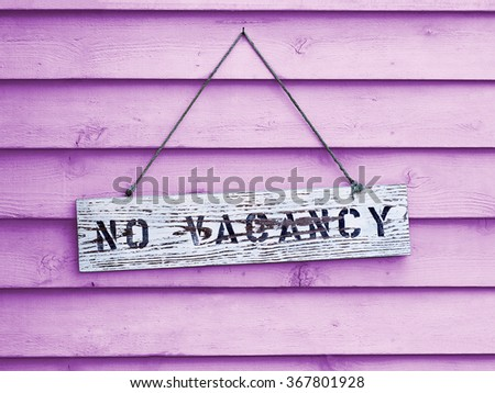 No Vacancy sign hanging on pink painted cedar siding. - stock photo