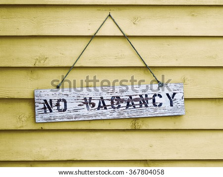 No Vacancy sign hanging on yellow painted cedar siding. - stock photo