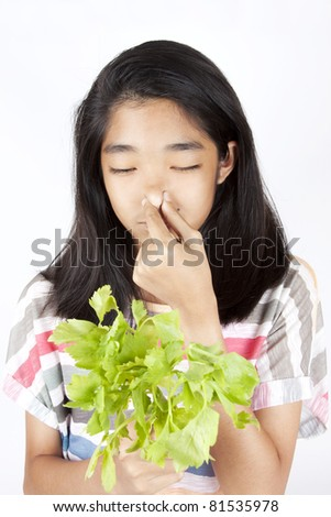 no veggie, Asian girl squeeze her nose for smelly celery. - stock photo