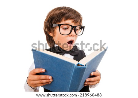 No way! Wide angle image of surprised little boy reading book and keeping mouth open while standing isolated on white - stock photo