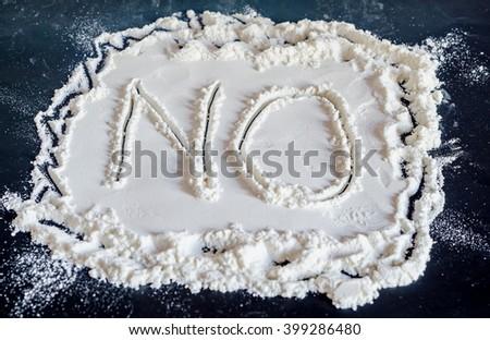 NO word write in white powder, black background, no drugs, close up. - stock photo
