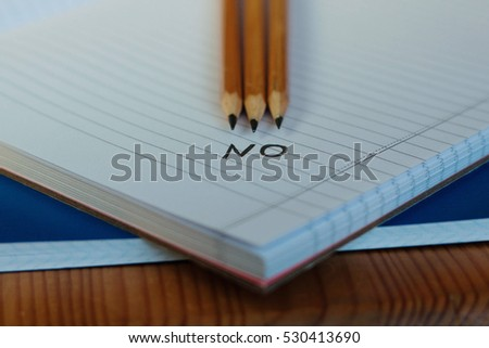 No word written on a notebook page and three pencils