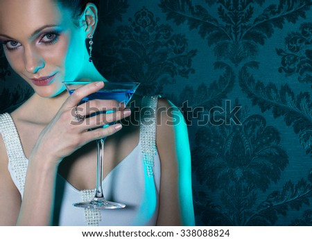 Noble beautiful woman in turquoise light on damask wallpaper background - stock photo