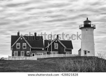 Nobska Point Lighthouse in black and white.  This picturesque lighthouse, located in Falmouth, Massachusetts, was established in 1829.  The current 40 ft. tower was built in 1876. - stock photo