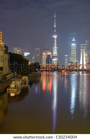 Nocturne view at Pudong with Oriental Pearl Tower, Financial and Jin Mao towers. In foreground illuminated bridge reflection in Suzhou Creek water. Long exposure.