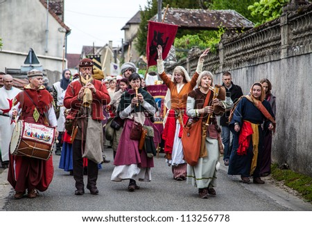 NOGENT LE ROTROU,FRANCE,MAY 19: Parade of medieval characters with old style band marching near the Saint Jean Castle during a historical reenactment festival on May 19,2012 in Nogent le Rotrou,France