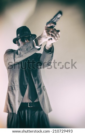 Noir Man Points Gun Up. Man in suit, hat and sunglasses pointing a gun upwards.