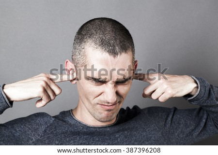 noise and hearing concept - stressed out young man plugging his ears to refuse listening to problems or stress, contrast effects