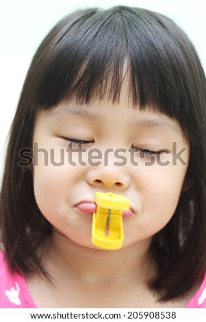 Noisy girl with lips pegged - stock photo