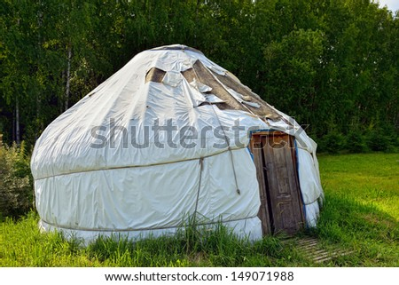 Nomadic Yurt in a forest clearing at sunset. Portable bent dwelling structure traditionally used by nomads in the steppes of Central Asia.  - stock photo