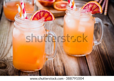 non-alcoholic blood orange cocktail in a glass jar on a wooden background - stock photo