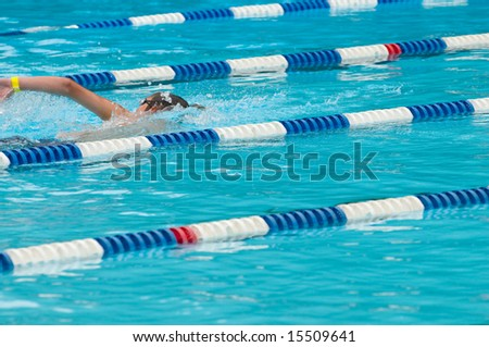 Non-identifiable swimmer in outdoor swimming pool with lane separators, blue and white floats (selective focus on swimmer) - stock photo