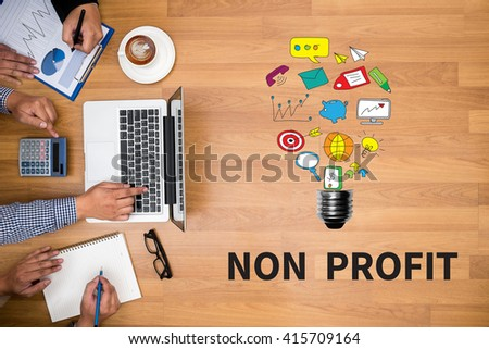 NON PROFIT Business team hands at work with financial reports and a laptop - stock photo