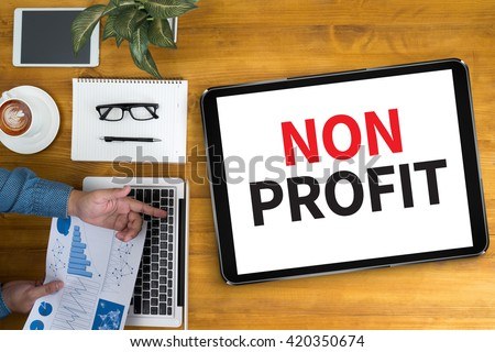 NON PROFIT Businessman working at office desk and using computer and objects, coffee, top view, - stock photo