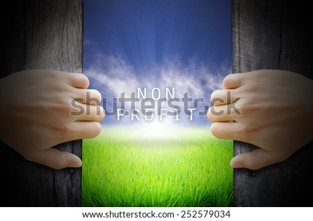 Non Profit concept. Hand opening an old wooden door and found a texts floating over green field and bright blue Sky Sunrise. - stock photo