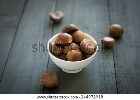 Non-roasted chestnuts in a white bowl -over the shoulder view - stock photo