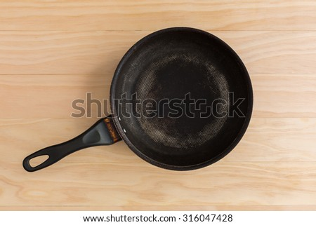 non stick frying pan on wooden background - stock photo