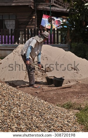 NONG KHAI, THAILAND - August 21, 2015: Worker take sand in to the bucket at building site in Nong Khai, Thailand